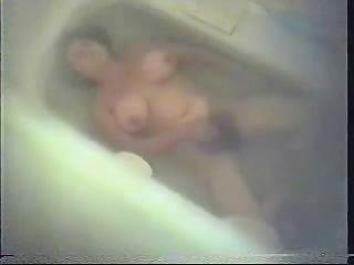 bushy woman dildoing into bathroom tube.